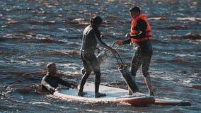 Type et fille dans des gilets de vie combattant avec les panneaux surfants de battes molles dans l'eau clips vidéos