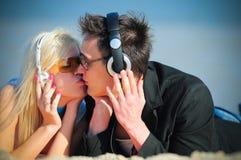 Type et fille dans le baiser d'écouteurs Photos libres de droits