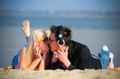 Type et fille dans le baiser d'écouteurs Photo libre de droits