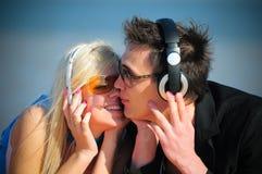 Type et fille dans le baiser d'écouteurs Photographie stock libre de droits