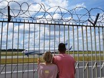Type et fille de couples de personnes dans l'amour regardant ensemble les avions de observation l'aéroport par la barrière avec l Image stock