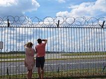 Type et fille de couples de personnes dans l'amour regardant ensemble les avions de observation l'aéroport par la barrière avec l Images stock