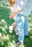 Type et fille de plan rapproché tenant des mains à l'arrière-plan d'herbe Photo stock