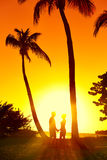 Type et fille de silhouette sur le coucher du soleil Photo libre de droits