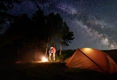 Type et fille embrassant par le feu sous le ciel étoilé lumineux qui est manière laiteuse évidente près de tente en bois Image stock