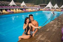 Type et fille posant contre la piscine avec de l'eau parfait aqua et prenant la photo de selfie avec le monopod sur la station de Image libre de droits