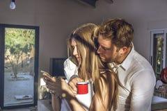 Type et fille regardant leurs téléphones portables à la maison Couples du type et de la fille regardant leur téléphone portable photographie stock libre de droits