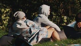 Type et fille s'asseyant sur un fauteuil poire sur l'herbe dehors en nature le jour d'été banque de vidéos