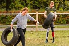 Type et fille s'exerçant avec un pneu Photo stock