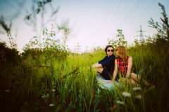 Type et la fille s'asseyant dans l'herbe Photographie stock
