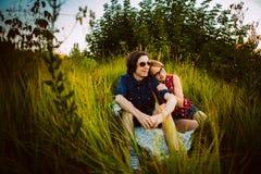 Type et la fille s'asseyant dans l'herbe Photo libre de droits