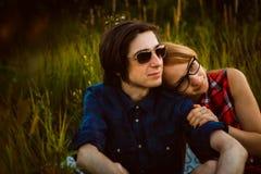 Type et la fille s'asseyant dans l'herbe Photo stock