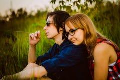 Type et la fille s'asseyant dans l'herbe Photos stock