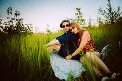 Type et la fille s'asseyant dans l'herbe Image libre de droits