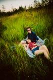 Type et la fille s'asseyant dans l'herbe Photographie stock libre de droits