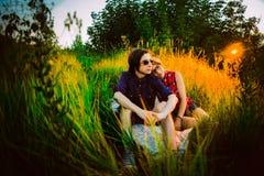 Type et la fille s'asseyant dans l'herbe Images stock