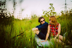 Type et la fille s'asseyant dans l'herbe Photos libres de droits