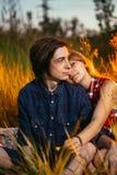 Type et la fille s'asseyant dans l'herbe sur un fond de coucher du soleil Photographie stock