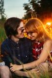Type et la fille s'asseyant dans l'herbe sur un fond de coucher du soleil Photo libre de droits