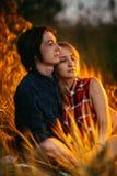 Type et la fille s'asseyant dans l'herbe sur un fond de coucher du soleil Photographie stock libre de droits