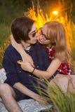 Type et la fille s'asseyant dans l'herbe sur un fond de coucher du soleil Photos libres de droits