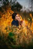 Type et la fille s'asseyant dans l'herbe sur un fond de coucher du soleil Photo stock