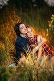 Type et la fille s'asseyant dans l'herbe sur un fond de coucher du soleil Image libre de droits