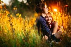 Type et la fille s'asseyant dans l'herbe sur un fond de coucher du soleil Image stock