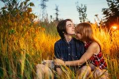 Type et la fille s'asseyant dans l'herbe sur un fond de coucher du soleil Images libres de droits