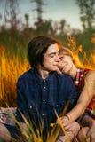 Type et la fille s'asseyant dans l'herbe sur un fond de coucher du soleil Images stock