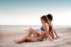 Type et son amie s'asseyant sur la plage Photographie stock