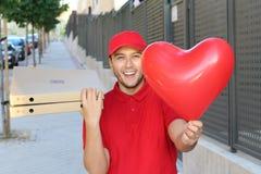 Type ethnique mignon de la livraison de pizza tenant le ballon en forme de coeur image stock