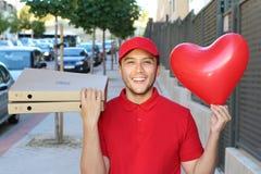 Type ethnique mignon de la livraison de pizza tenant le ballon en forme de coeur images libres de droits