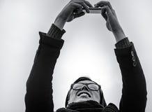 Type faisant le selfie sur le smartphone, noir et blanc, extérieur Images libres de droits