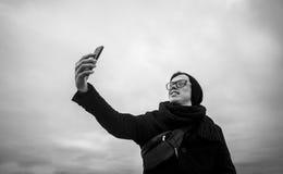 Type faisant le selfie sur le smartphone, noir et blanc, extérieur Photo libre de droits