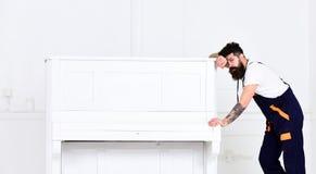 Type fatigué avec le bras tatoué se penchant sur le piano Moteur beau essayant d'effectuer l'instrument de musique en bois lourd Photos stock