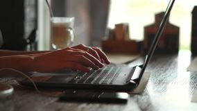 type femelle des mains 4k sur le clavier d'ordinateur portable touchant le touchpad avec le téléphone intelligent de doigts se tr banque de vidéos