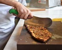 A type of flatbread Turkish pide is being sliced royalty free stock photography