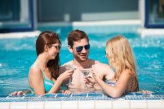 Type flirtant avec deux femmes à la piscine, buvant photographie stock libre de droits