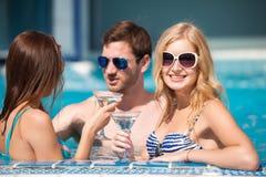 Type flirtant avec deux femmes à la piscine, buvant photo libre de droits
