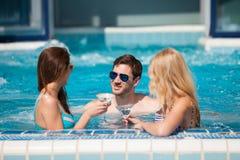 Type flirtant avec deux femmes à la piscine, buvant photos libres de droits