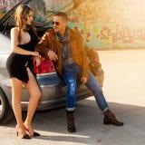 Type flirtant avec une fille s'asseyant dans un tronc de voiture Images stock