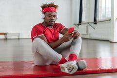 Type folâtre attentif se reposant après la formation intense tout en regardant sur le smartphone image stock