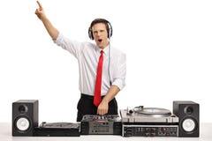Type formellement habillé gai jouant la musique sur une plaque tournante photographie stock libre de droits