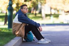 Type frais s'asseyant et détendant dehors pendant une coupure dans la classe photos libres de droits
