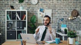 Type gai écoutant la danse de chant de musique au travail utilisant des écouteurs clips vidéos