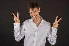 Type gai beau souriant dans une chemise sur un fond noir Image stock