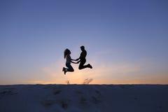 Type gai et fille ayant l'amusement et dansant sur la dune de sable Images stock