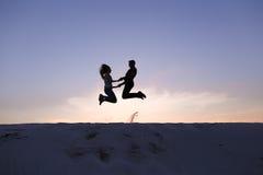 Type gai et fille ayant l'amusement et dansant sur la dune de sable Photographie stock