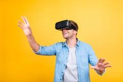 Type gai et heureux dans les lunettes de port de réalité virtuelle de chemise de jeans Photo libre de droits